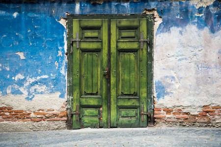 A very old green door and a brick wall destroyed by weather and years ideal for photo sessions background