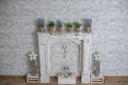 Spring summer decor with wood fireplace, lavender, basil, oregano, rosemary and flowers for studio photography