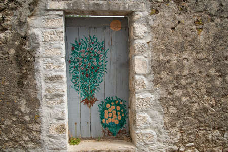 Old, painted wooden door of a ruined stone building from Roman times, Krk town, Croatia. Ideal image for photo background