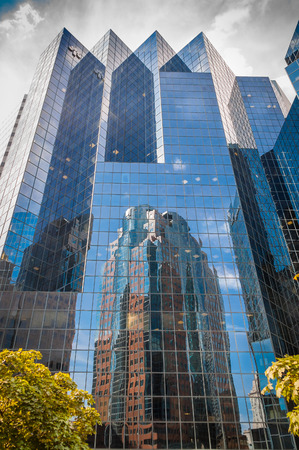 glass building in downtown Montreal, with reflection of Reviews another building