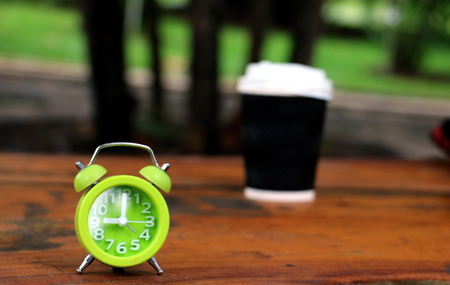pm: green clock and cup of coffee on wood black ground.