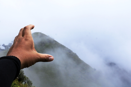 Man hand sign on Mountain background. A man travel on forest  and show hand in fright.he make sigh going to mountain.