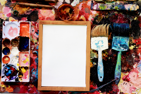 paint brushes and drawing paper on a colorful background.
