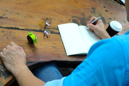 body part. In the morning a man sitting and writing on note book  in public park.