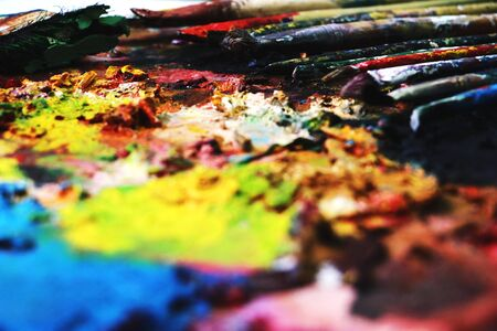 Close up paint brushes on a color full painter in black ground.  写真素材