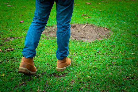 Body part a man wearing jean and walking.He is walking on grass in public park.going,walking,objective,goal. Banque d'images