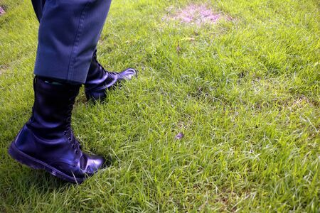 Body part a man walking.He walking on grass background.He wear black shoes.going,move on,fright,develop,Grow up.