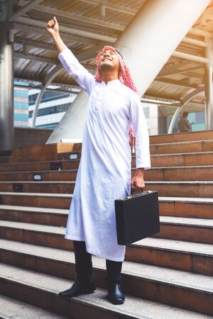 Muslim Arab man.He is raise hand and holding business Bag.He is smile and standing in town.Succeed,finish,Photo concept Arab man and portrait.