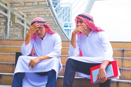 In the staircase. Islamic Business man  crying. They are Sorry from losing business.They are Enormous loss. Photo concept Business. 版權商用圖片