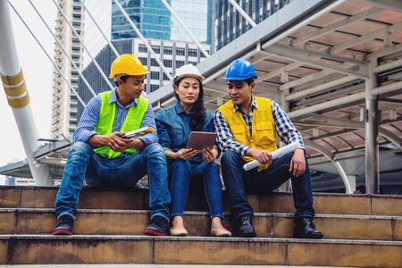 Working engineer. They are talking and plant for work with equipment beside building background. woman talking with a man plant for work. They sitting  on staircase. Photo concept for engineering. 写真素材