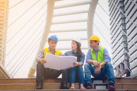 Working engineer. They are talking and plant for work with equipment beside building background. woman talking with a man plant for work. They sitting  on staircase. Photo concept for engineering. 版權商用圖片