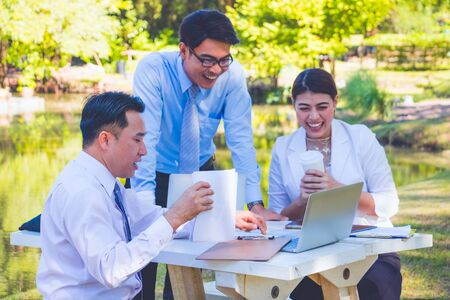 Business team work.They are sitting on bench and talking in the park.they are talking about business and on table had a notebook and a glass of coffee.Photo concept business and team work.