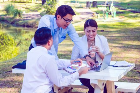Business team work.They are sitting on bench and talking in the park.they are talking about business and on table had a notebook and a glass of coffee.Photo concept business and team work. Zdjęcie Seryjne
