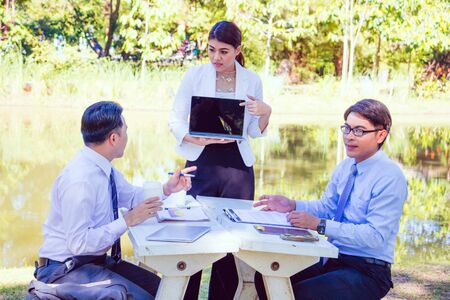 Business team work.They are sitting on bench and talking in the park. they are talking about business and on table had a notebook and a glass of coffee.Photo concept business and team work. Zdjęcie Seryjne