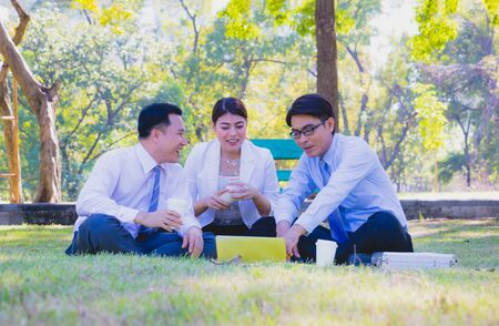 Business team work.They are talking in the park.they are talking about business and on the floor had a notebook and a glass of coffee.Photo concept business and relax time.