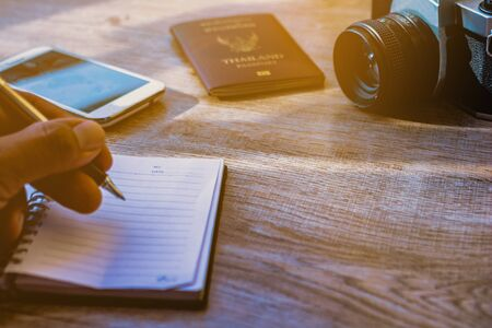 Hand holding a pen and notebook. Men are writing recorded on notebook a daily basis. Camera Phones and Accessories on old wood.