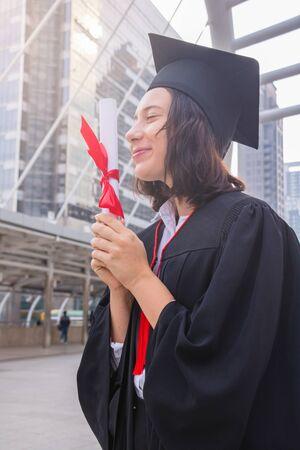 她是毕业生佩戴毕业生的礼服。她站立和秀学位证书。她是庆祝教育毕业。她很高兴。照片概念教育和成功。