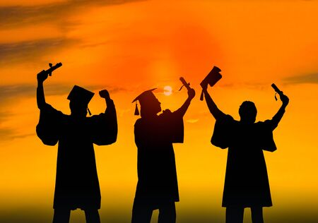 Silhouette of Student Graduation. They are seeing sunset.They are standing and show hand.They are celebration in Graduate , Education,academic,Photo concept Silhouette and Success