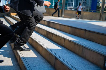 Body part business man.they are wearing black suit and carry a briefcase.They are running/walking  on staircase. Life a hurry and Business competition.Photo concept  business and succeed. Фото со стока - 147148027