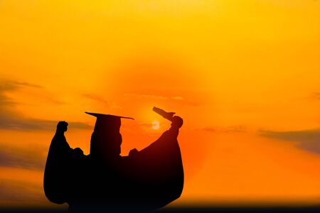 Silhouette photo.He s wearing  graduate's dress.He is standing and show hand.He is celebration education Graduation.He is happy in good time.