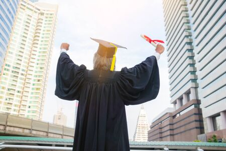 Body part.A man is wearing  graduate's dress.He is standing and show hand. He is celebration education Graduation.He is very happy in good time.Photo concept succeed and graduate.