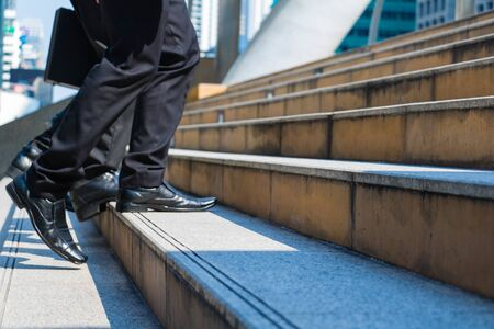 Body part business man.they are wearing black suit and carry a briefcase.They are running/walking  on staircase. Life a hurry and Business competition.Photo concept  business and succeed.