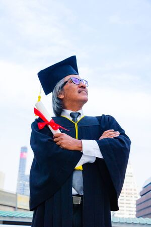 He is  wearing  graduate's dress and standing and show hand. He is celebration education graduation . He is happy in good time. Photo concept  Education and success. Фото со стока