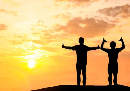 Silhouetted photo.They are standing and holding their hand together.They are enjoying and also they are watching the evening glow together.Photo concept for happy and teamwork.