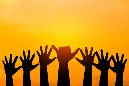 Silhouetted of hand photo.Hand show up in to sky  with sunset.Hand is symbol Comment and democratic.