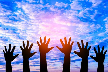 Silhouetted of hand photo.Hand show up in to sky with sunset.Hand is symbol Comment and democratic. Imagens