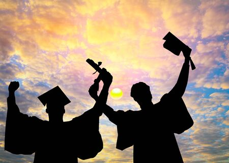 Silhouette of Student Graduation. They are seeing sunset. They are standing and show hand.Photo concept Silhouette and Success.
