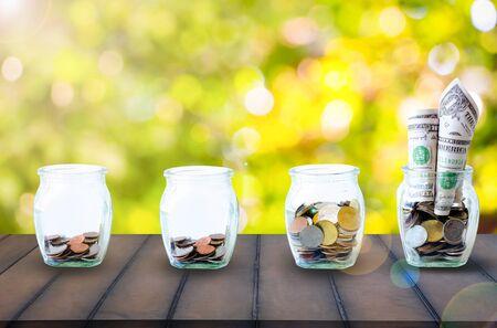 Die Münzen in der Flasche auf Himmelshintergrund. Die Strahlensonne auf den Münzen in der Flasche auf altem Holz. Das Konzept des Wachstums für das Geld sparen.