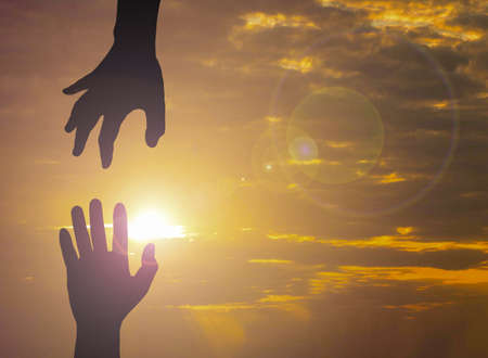 The Silhouette photo of hand to hand. One hand helps another. This photo communicate about hope and supporting and also helping. International day of peace. Reklamní fotografie