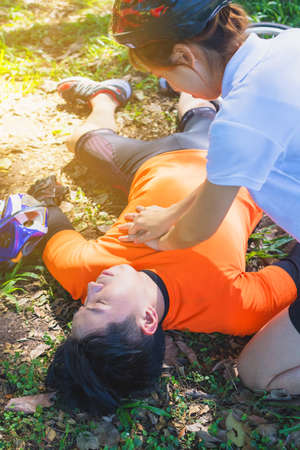 First Aid Emergency is CPR.The man who face heart attack and shock was helped by his friend after the bicycle race. A woman who is his friend give CPR to save his life.Photo concept Emergency and CPR. 免版税图像