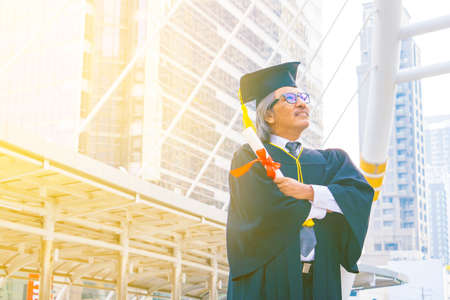 He is wearing graduate's dress and standing and show hand.He is celebration education graduation.He is happy in good time.Photo concept  Education and success.