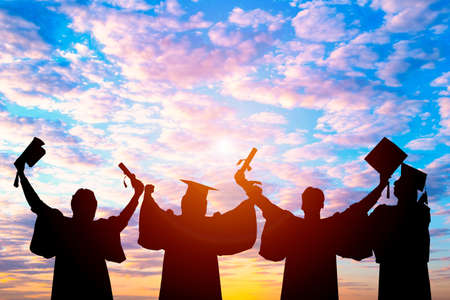 Silhouette of Student Graduation. They are seeing sunset.They are standing and show hand.They are celebration in Graduate, Education,academic, Photo concept Silhouette and Success. 版權商用圖片