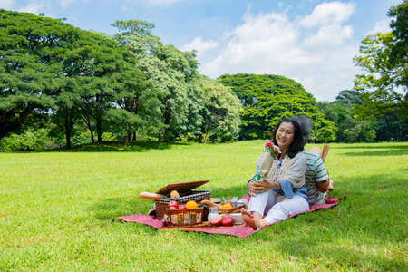Young Asian in park. they are having a picnic and relax time.A man sent apple for woman. She is  lying on the grass beside picnic basket. Photo lifestyle and picnic idea.