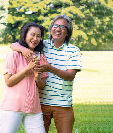 Asian woman relax time in park. A man sent milk for woman.She is drinking milk.She is  smile and be happy in good time ,Life style,Photo concept  exercise and healthy.