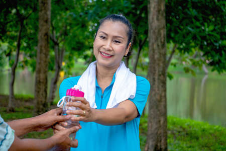 Asian woman relax time in park. A man sent water for woman.She is drinking water.She is smile and be happy in good time ,Life style,Photo concept exercise and healthy.