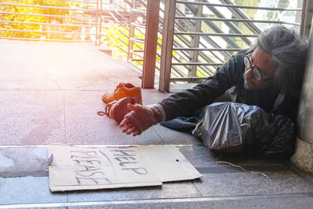 Homeless man is sitting down on walkway in town. He is hugging paper home. He is  hoping to have the better life. poverty, despair, Photo Sympathetic and hope concept. Stock fotó