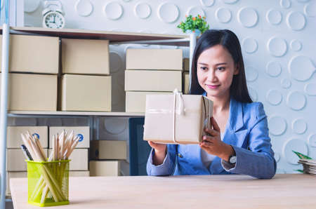 The young Asia Businesswoman makes parcel.She makes it for order online.She is happy and smiles.Gift , Business,work woman,Freelance,happy,pleasure.Photo concept work and Shopping.
