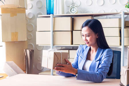 The young Asia Businesswoman makes parcel.She makes it for order online.She is happy and smiles.Gift,Business,work woman,Freelance,happy,pleasure.Photo concept work and Shopping.