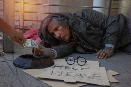 Homeless man is sitting down on walkway in town.He is receive dollar.He is hoping to have the better life. poverty, despair, Photo Sympathetic and hope concept. Imagens