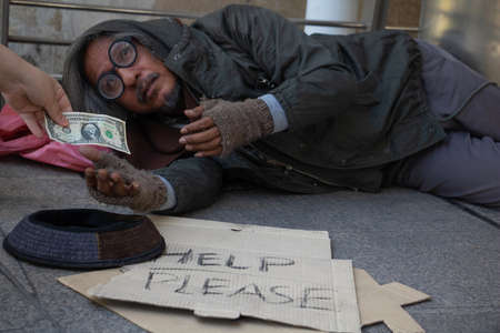 Homeless man is sitting down on walkway in town.He is receive dollar.He is hoping to have the better life. poverty, despair, Photo Sympathetic and hope concept. Banque d'images