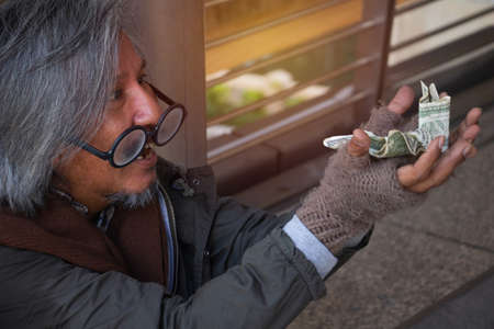 Homeless man is sitting down on walkway in town.He is receive dollar.He is very glad and happy. poverty, despair, Photo Sympathetic and hope concept. Stock fotó