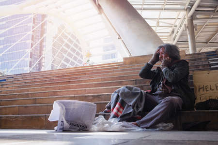Homeless man is sitting down on staircase and walkway in town. He is eating bread. He is very unhappy. poverty, despair, Photo Sympathetic and hope concept.