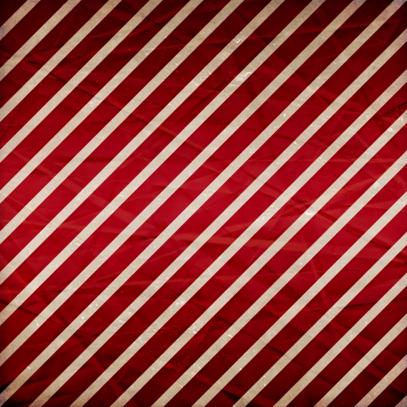 A crumpled  paper in a red and white stripe pattern for use as a background  photo