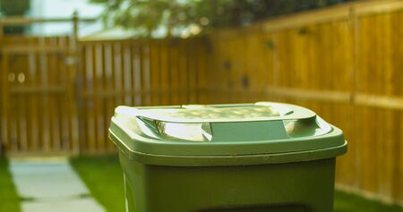Recycling garbage green basket on a back yard