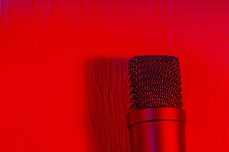 Microphone on lay on a texture background with a red light Stockfoto