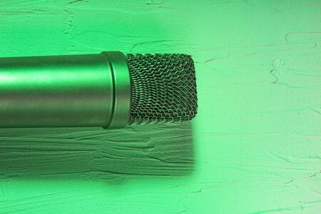 Microphone on lay on a texture background with green light Reklamní fotografie